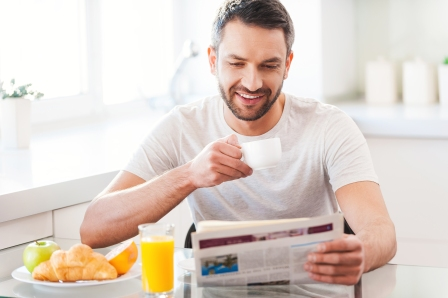 Handsome young man reading newspaper and smiling while drinking coffee and having breakfast in the kitchen